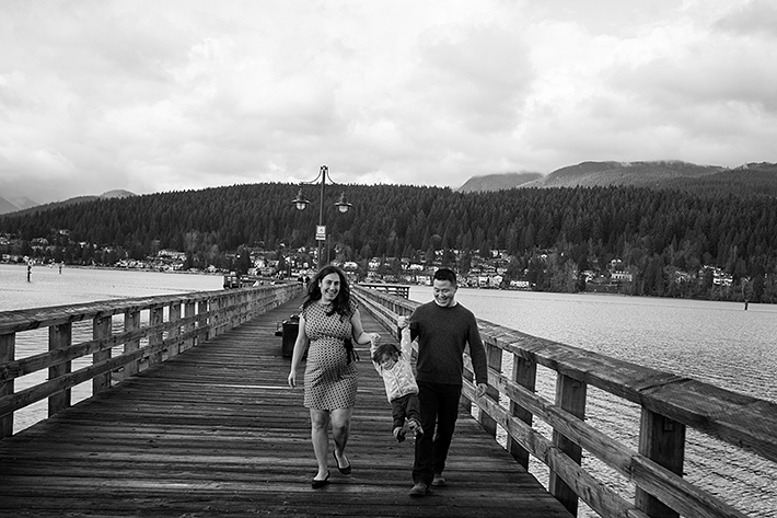 a family photo of them walking on the boardwalk with mountains in port moody, bc