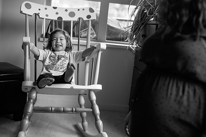 a pregnancy photo of the mom sitting with her daughter by the rocking chair in port moody, bc