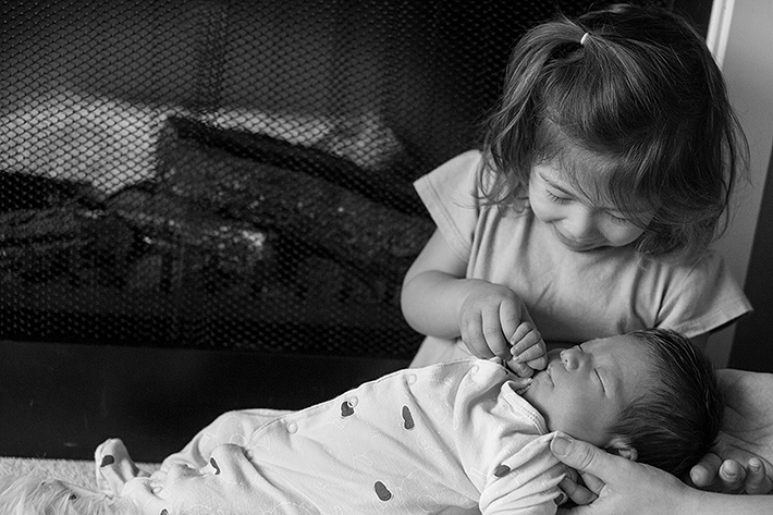 a new born photo being held by his sister in port moody, bc