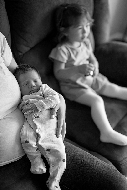 a new born photo watching tv with his sister in port moody, bc