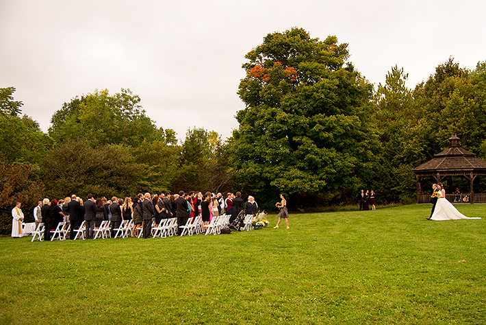 a wedding photo of the ceremony with the bride and father walking up the aisle at the outdoor ceremony arboretum in guelph ontario