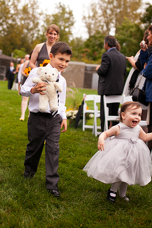 a wedding photo of the ceremony with a child holding ring bear at the outdoor ceremony arboretum in guelph ontario