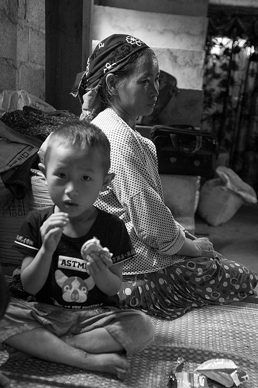 a travel photo from northern vietnam plan canada foster family. mother sitting on the bed with her son