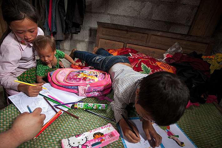 a travel photo from northern vietnam plan canada foster girl colouring with her siblings on the bed at home