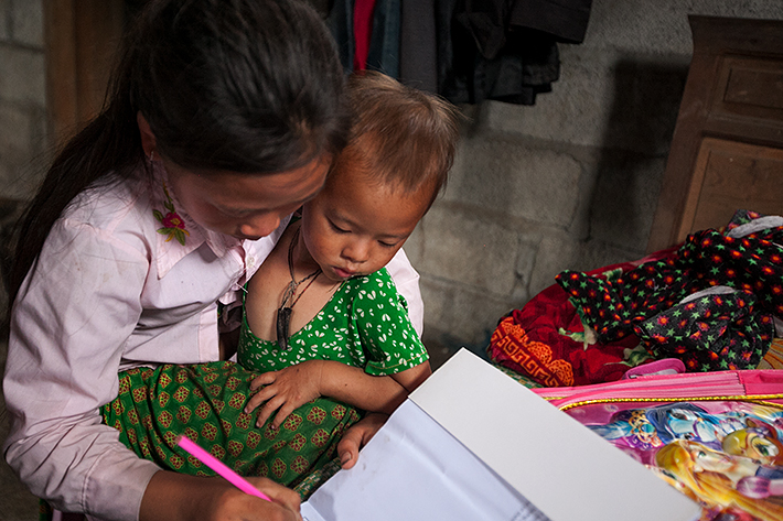 a travel photo from northern vietnam plan canada foster girl colouring with sister inside her family's home