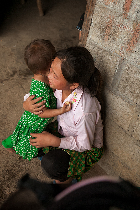 a travel photo from northern vietnam plan canada foster girl giving her sister a hug outside her family's home