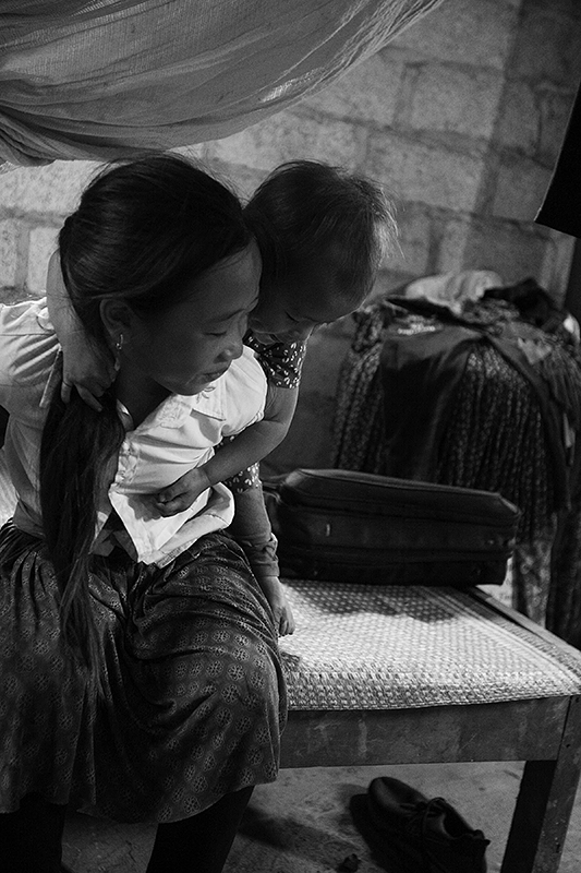 a travel photo from northern vietnam plan canada foster girl giving her sister a piggy back ride inside her family's home