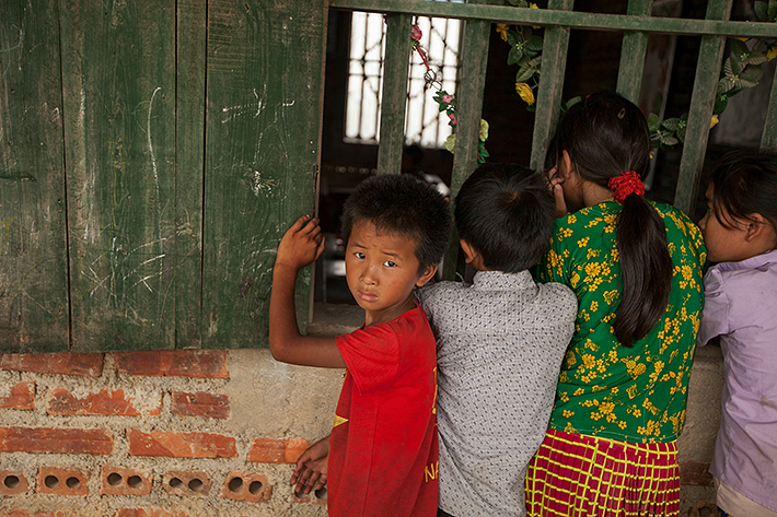 a travel photo from northern vietnam plan canada boy looking at camera while girls watch at school