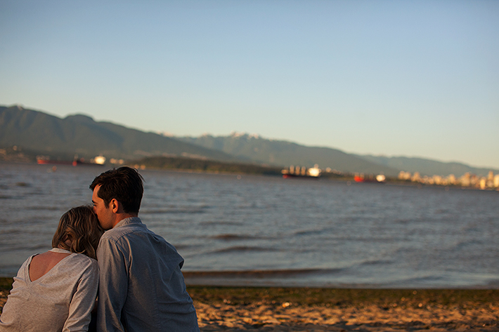 a spring engagement photo of a couple sitting cuddling at spanish banks beach at sunset in vancouver british columbia