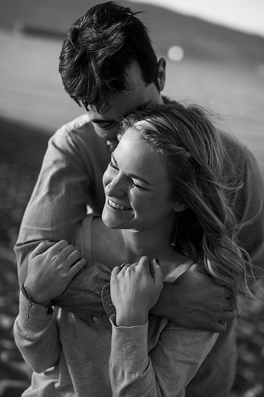 a spring engagement photo of a couple laughing at spanish banks beach vancouver british columbia