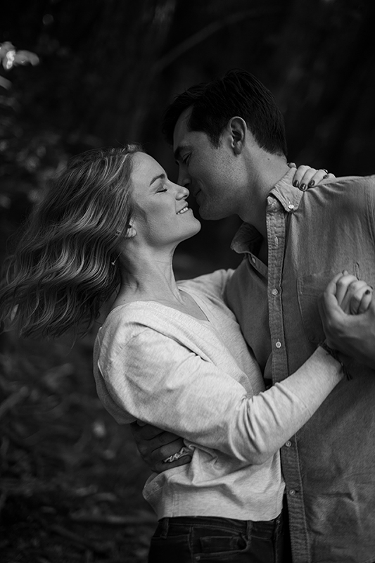 a spring engagement photo of a couple dancing at pacific spirit park vancouver british columbia