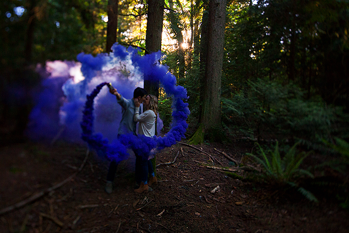 a spring engagement photo of a couple kissing with smoke bomb rings at pacific spirit park vancouver british columbia