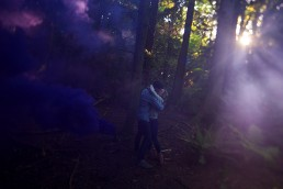a spring engagement photo of a couple kissing with smoke bombs at pacific spirit park vancouver british columbia