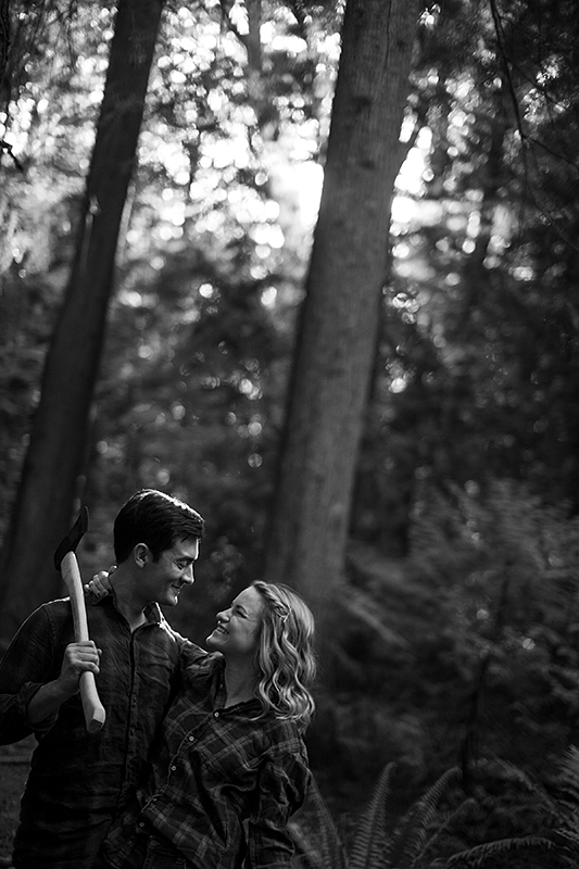 a spring engagement photo of a couple laughing holding an axe at pacific spirit park vancouver british columbia