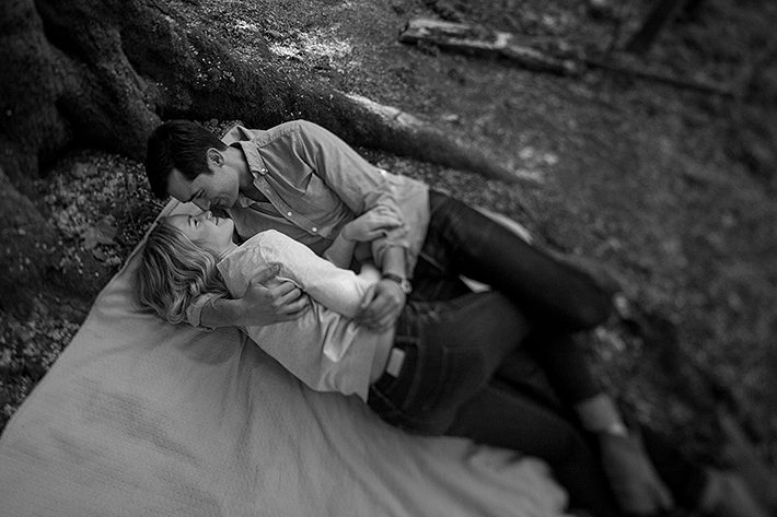 a spring engagement photo of a couple laying down cuddling at pacific spirit park vancouver british columbia
