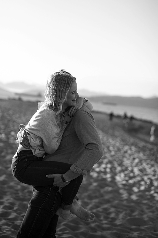 a spring engagement photo of a couple piggy back ride at spanish banks beach vancouver british columbia