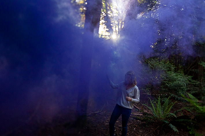a spring engagement photo of a the bride to be with smoke bombs at pacific spirit park vancouver british columbia