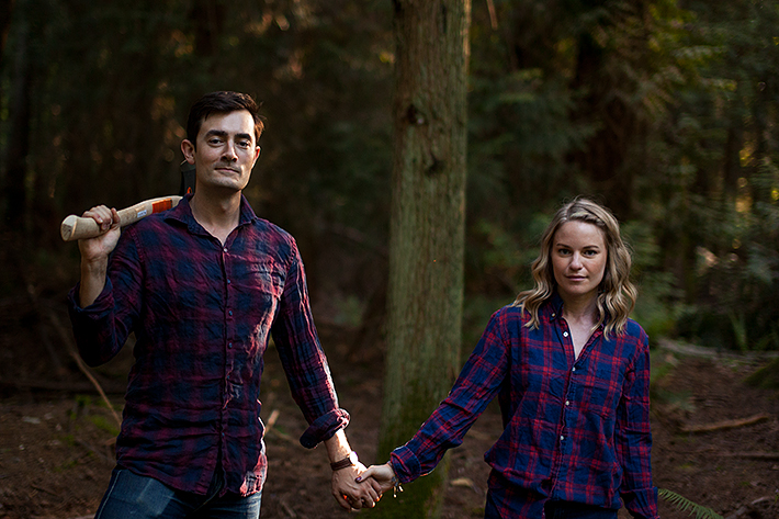 a spring engagement photo of a couple standing holding an axe at pacific spirit park vancouver british columbia