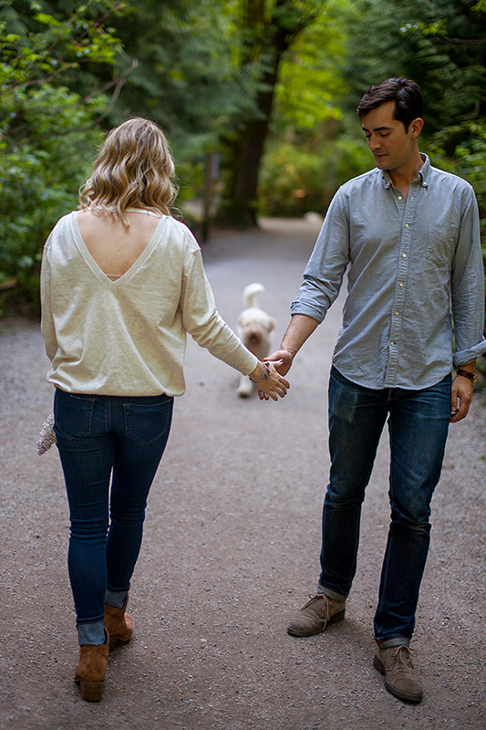 a spring engagement photo of a couple walking with their dog at pacific spirit park vancouver british columbia