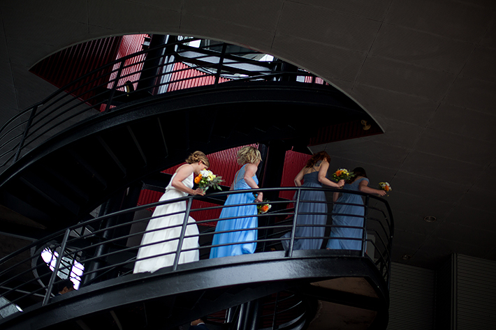 a summer wedding photo of the bridesmaids walking up stairs at the false creek yacht club on granville island vancouver british columbia