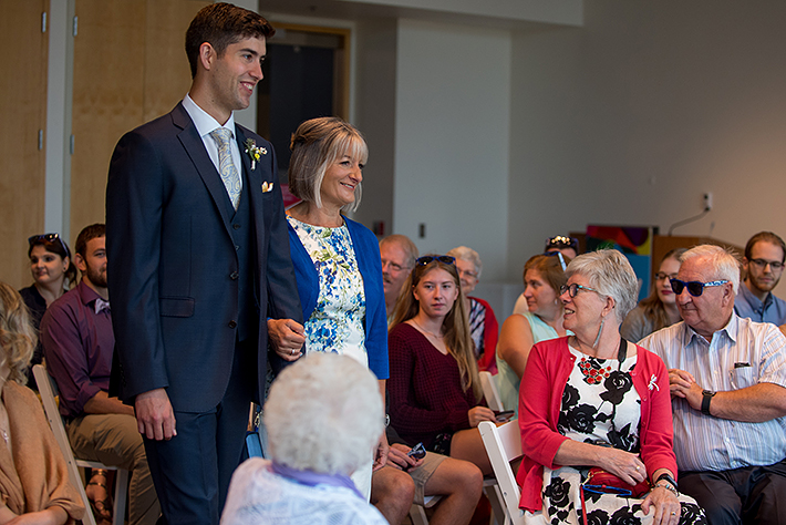 a summer wedding photo of the groom walking down the aisle with her mother at the museum of vancouver british columbia