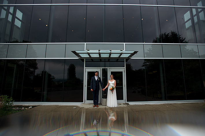 a summer wedding photo of the couple holding hands at the museum of vancouver british columbia