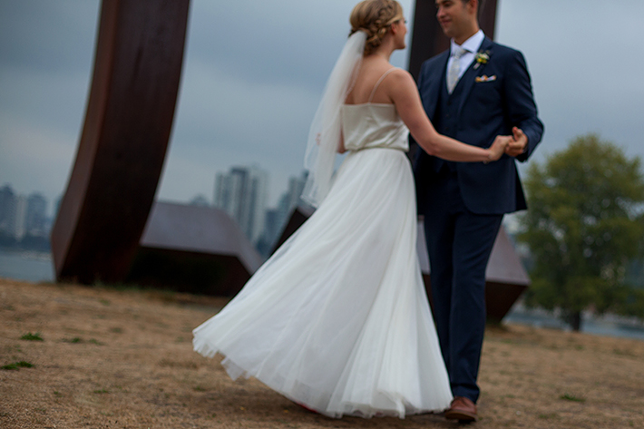 a summer wedding photo of the couple dancing in front of an art installation of vancouver british columbia