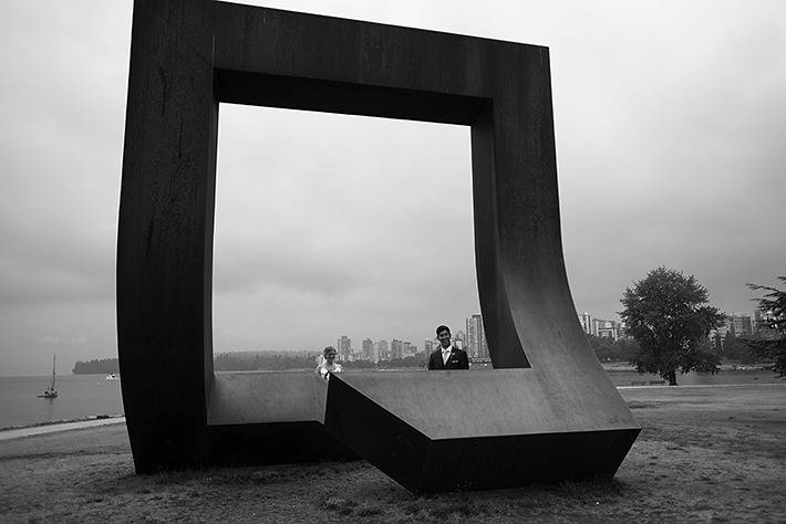 a summer wedding photo of the couple standing in front of an art installation of vancouver british columbia