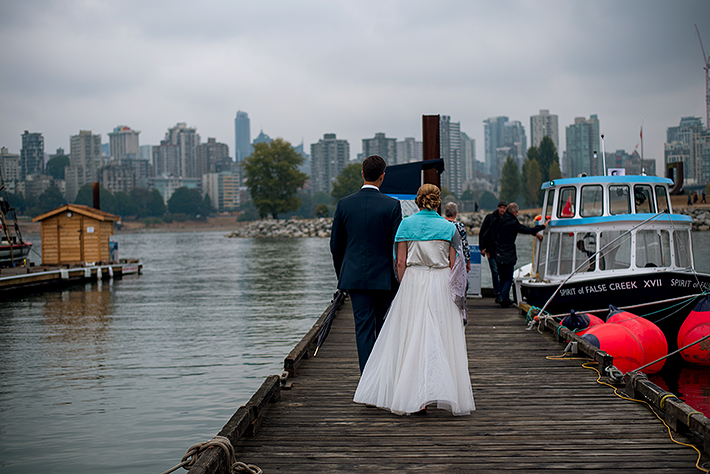 a summer wedding photo of the couple walking to the ferry at the false creek yacht club on granville island vancouver british columbia