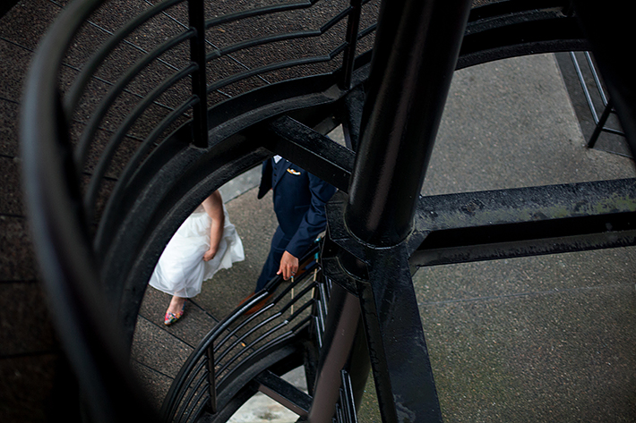 a summer wedding photo of the couple walking on stairs at the false creek yacht club on granville island vancouver british columbia