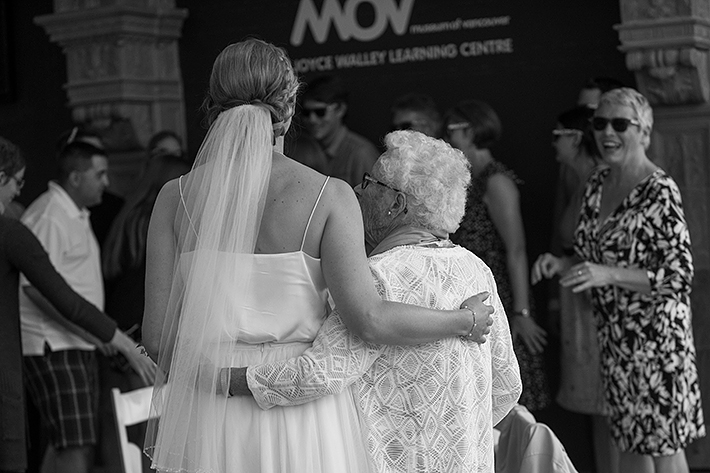 a summer wedding photo of the bride hugging grand mother at the museum of vancouver british columbia