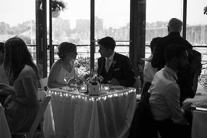 a summer wedding photo of the couple in silhouette at the false creek yacht club on granville island vancouver british columbia
