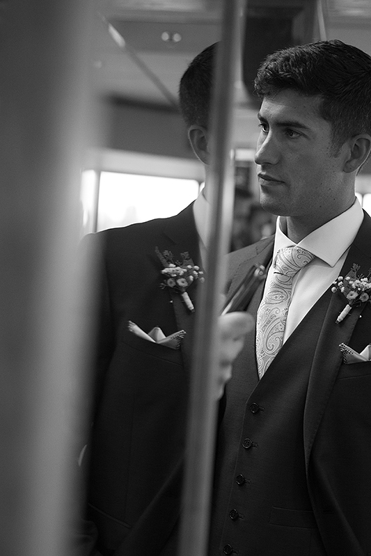 a summer wedding photo of the groom in reflection at the false creek yacht club on granville island vancouver british columbia