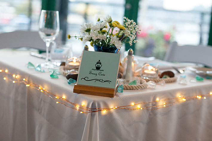 a summer wedding photo of the head table at the false creek yacht club on granville island vancouver british columbia