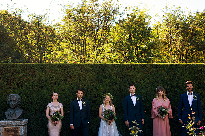 a summer wedding party photo beside a statue in vandusen gardens in vancouver british columbia