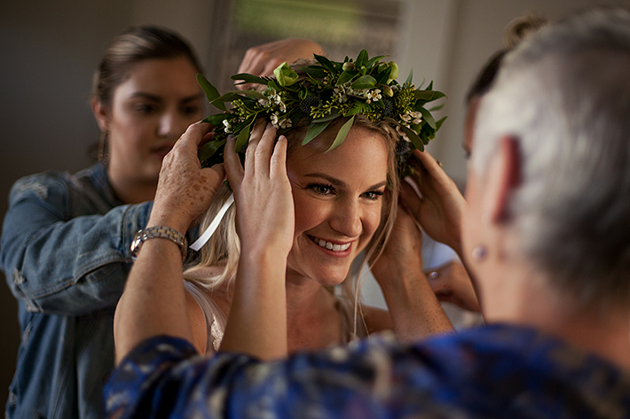 a summer wedding of the bride putting on her flower crown in vancouver british columbia