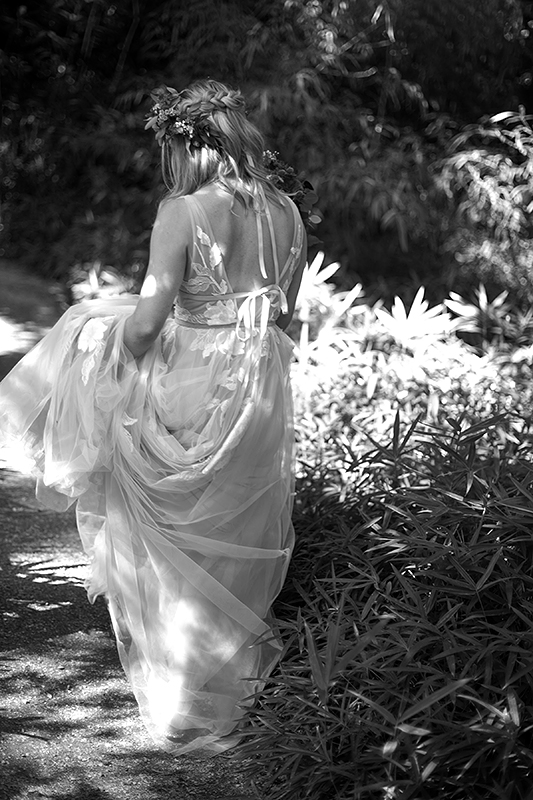 a summer wedding photo of the bride walking in vandusen gardens in vancouver british columbia
