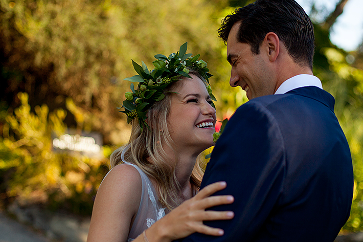 a summer wedding photo of a couple laughing in tall grass in vandusen gardens in vancouver british columbia