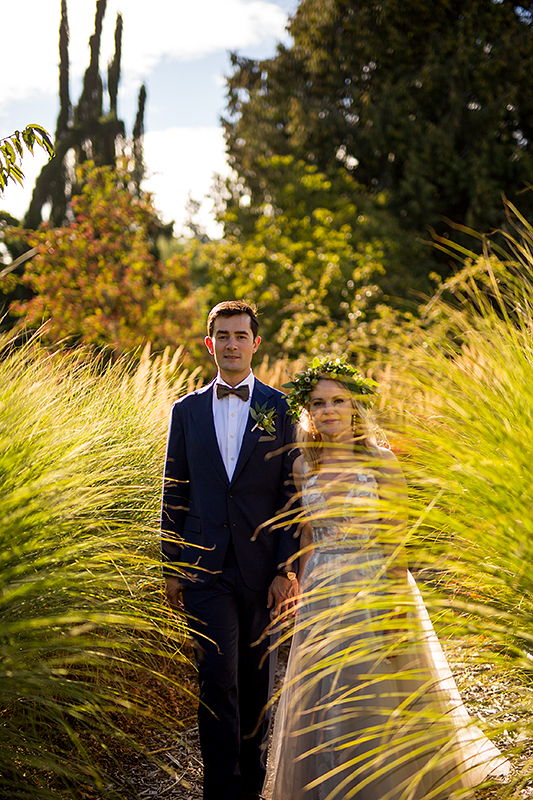 a summer wedding photo of a couple standing in tall grass in vandusen gardens in vancouver british columbia
