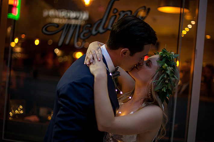 a summer wedding photo of a couple kissing with twinkle lights at medina cafe vancouver british columbia