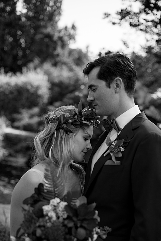 a summer wedding photo of a couple in tall grass in vandusen gardens in vancouver british columbia