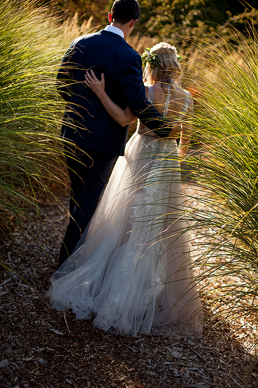 a summer wedding photo of a couple walking in tall grass in vandusen gardens in vancouver british columbia