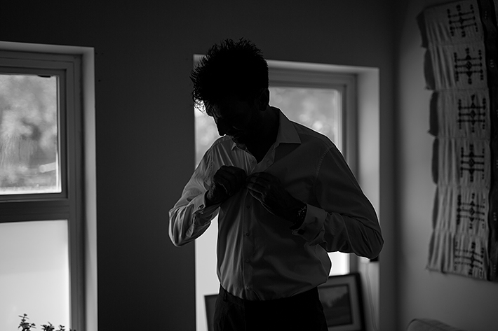 a summer wedding photo of the groom getting ready in vancouver british columbia