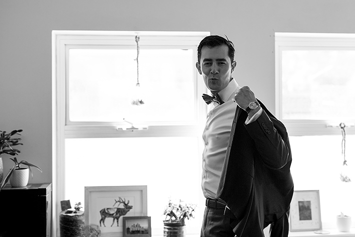 a summer wedding photo of the groom putting on his jacket making a funny face in vancouver british columbia