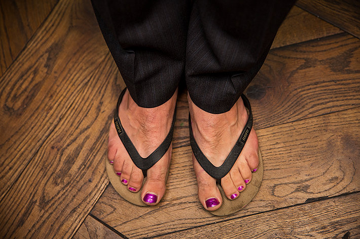 a summer wedding photo of the grooms toe nail polish with flip flops at medina cafe vancouver british columbia