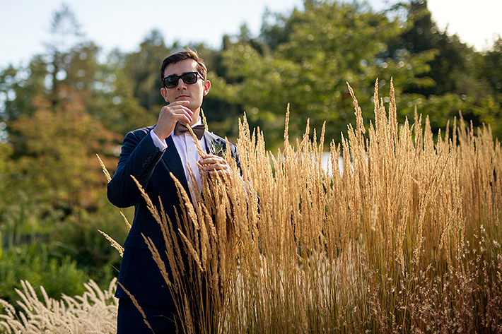 a summer wedding photo of the groom in tall grass in vandusen gardens in vancouver british columbia