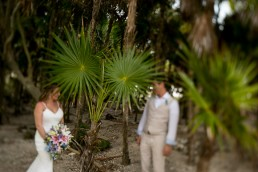 a photo of the couple in a palm forest at a destination wedding in cancun mexico