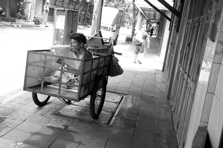 a travel photo of a man in a cart in bangkok thailand