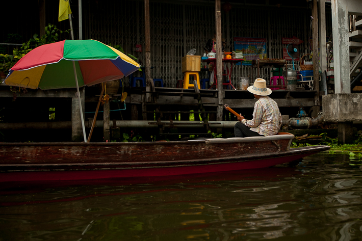 a travel photo of a man with umbrella in the floating market in bangkok thailand