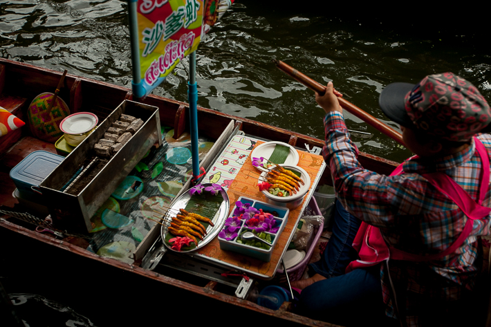 a travel photo of a food vendor in the floating market in bangkok thailand